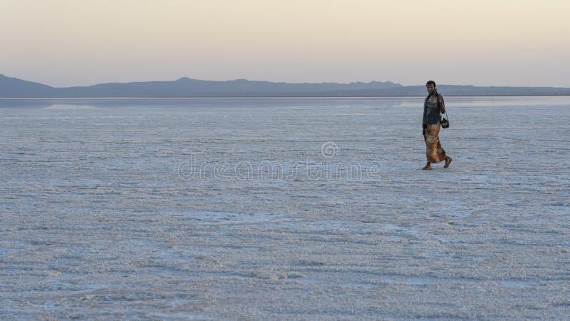 在远处走在Asale湖盐平原的日落期间的战士Danakil消沉的在埃塞俄比亚,非洲 图库摄影