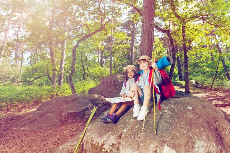 在远足男孩期间的休息和女孩坐石头 库存照片