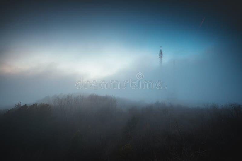 在连接的有薄雾的雾和在山的无线电铁塔 库存图片