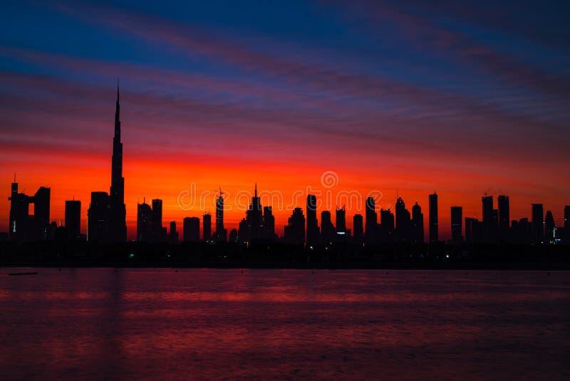 在迪拜的神话血淋淋的红色天空 黎明、早晨、日出或者黄昏在哈里发塔 美丽的色的多云天空  库存图片