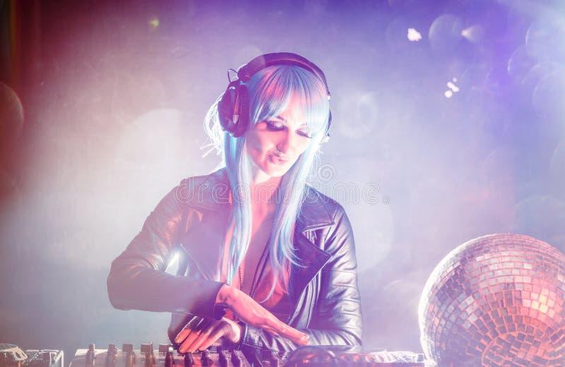 在迪斯科俱乐部的妇女DJ混合的纪录 库存图片