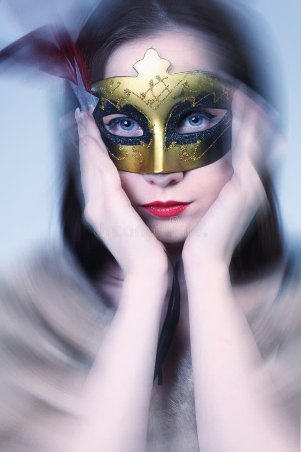 在迷离背景的妇女佩带的狂欢节威尼斯式屏蔽。   免版税图库摄影