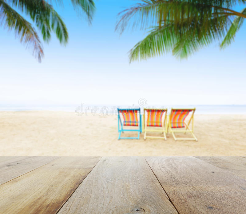 在迷离海滩背景的木台式与海滩睡椅在椰子树下 免版税库存图片