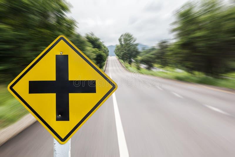 在迷离路背景的前面交叉点标志 免版税图库摄影