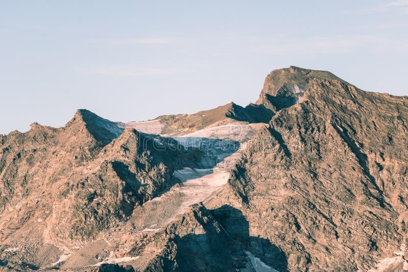 在退休的死的冰川的日落光在意大利法国阿尔卑斯 气候变化概念 被定调子的成为不饱和的图象 免版税库存图片