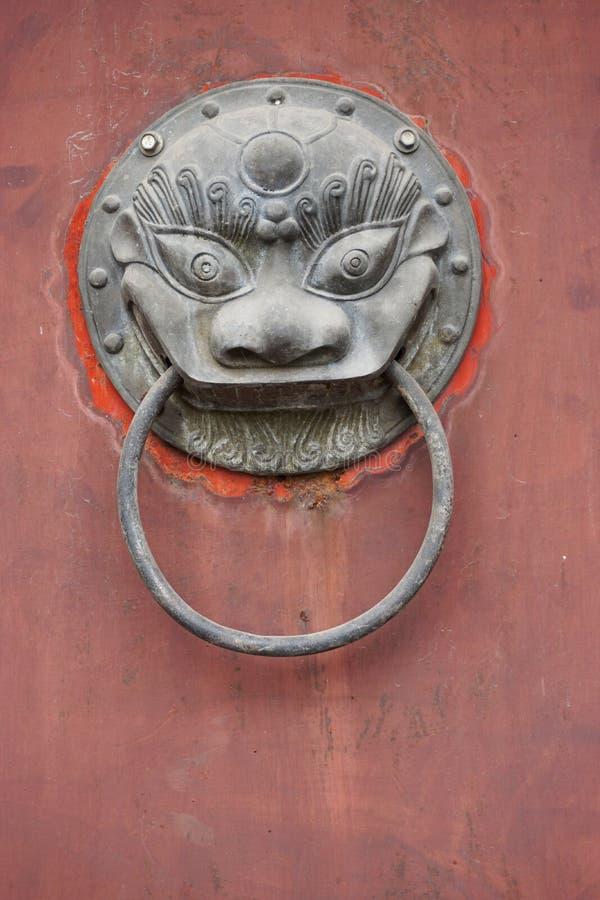 在退色的红色门的葡萄酒古色古香的古铜色通道门环 库存图片