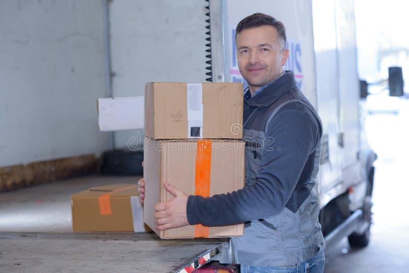 在送货卡车的仓库工作者移动的纸盒 免版税库存照片