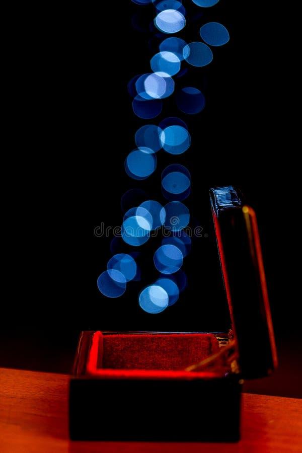 在逃脱从箱子的黑背景的蓝色bokeh圈子 免版税库存照片