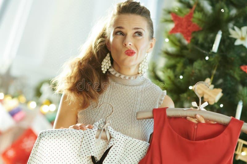在选择欢乐圣诞节成套装备的圣诞树附近的妇女 库存图片