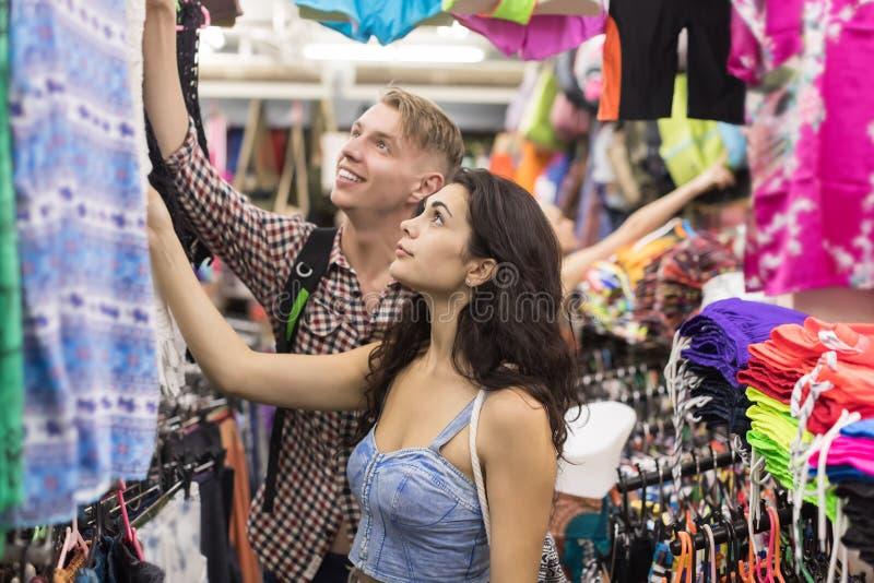 在选择衣裳、男人和妇女买家愉快微笑在零售店的购物的年轻夫妇 库存图片