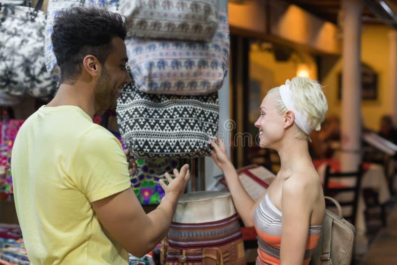 在选择袋子、男人和妇女愉快微笑在零售店的购物的年轻夫妇 免版税库存图片