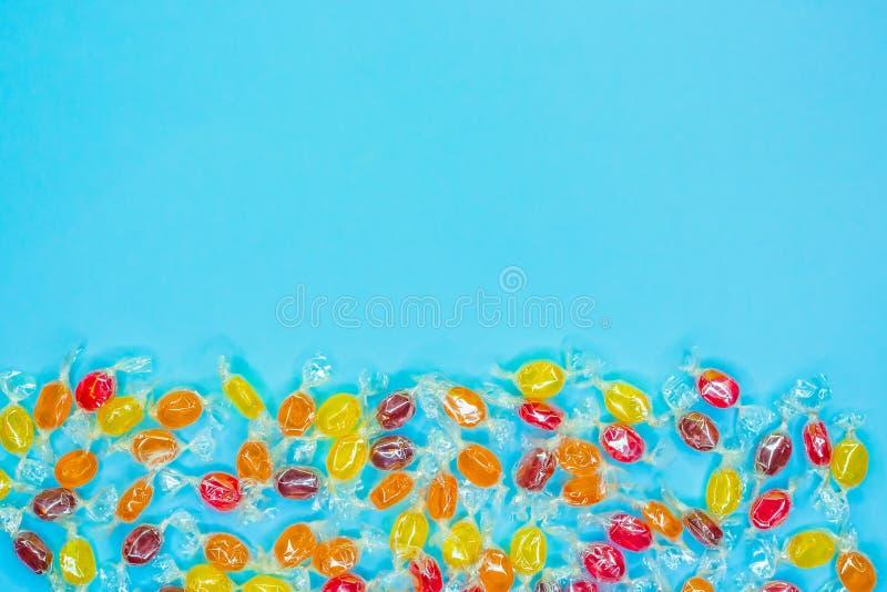 在透明云母封皮,在蓝色背景的甜点的明亮的多彩多姿的糖果,五颜六色的糖果驱散了,顶视图与 图库摄影
