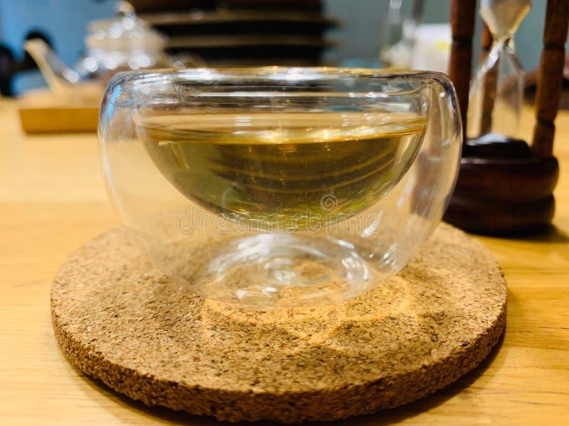在透明双层壁玻璃里面的热的清凉茶在木桌上把放的浅褐色的木盘子 免版税库存照片