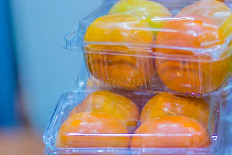 在透明塑料盒的成熟黄色东方或日本柿子待售在市场上 在塑料b的新鲜的柿子果子 免版税库存图片