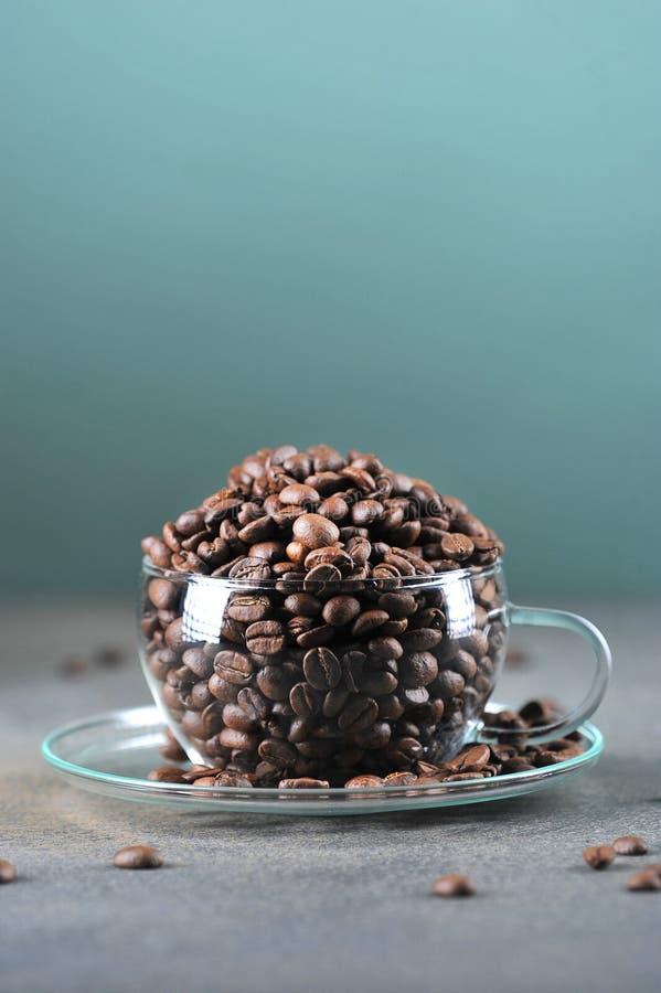 在透明玻璃杯的咖啡豆在灰色绿色 免版税库存图片