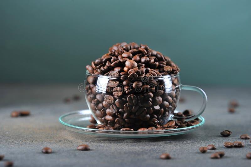 在透明玻璃杯的咖啡豆在灰色绿色 免版税图库摄影