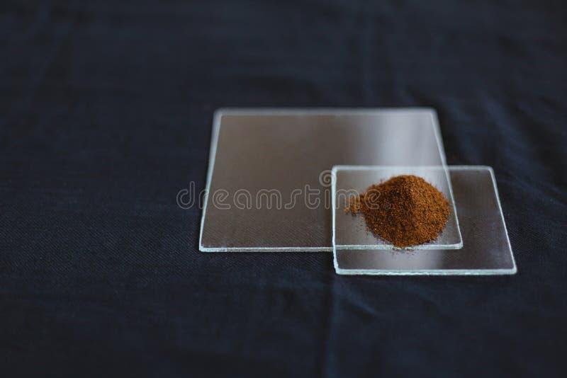 在透明玻璃瓶子的东方香料在一张黑桌布 免版税库存照片