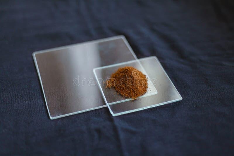 在透明玻璃瓶子的东方香料在一张黑桌布 库存照片