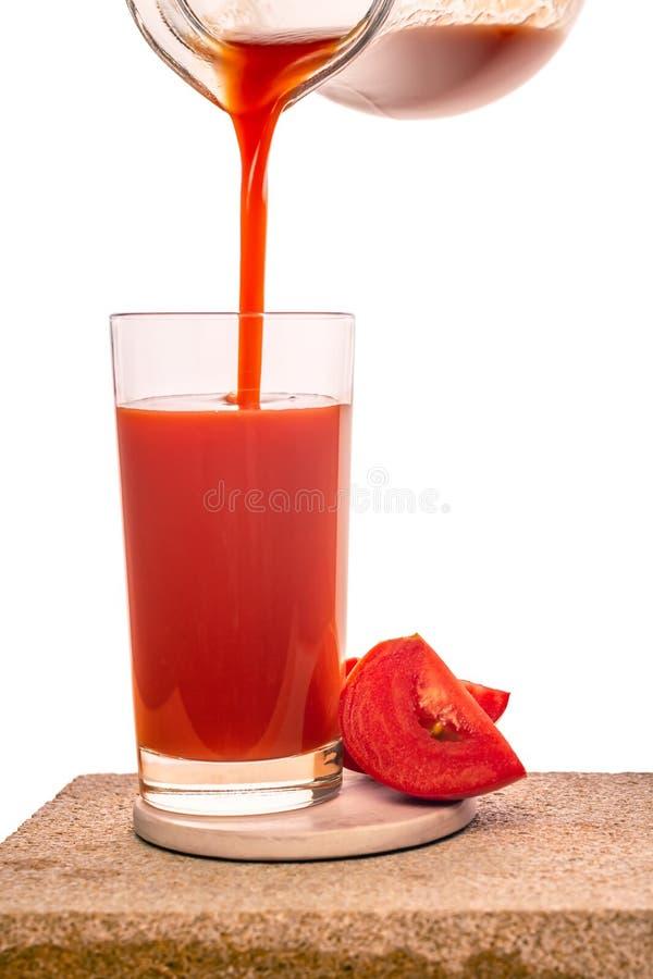 在透明玻璃的倾吐的西红柿汁装饰了在白色背景隔绝的菜 库存图片
