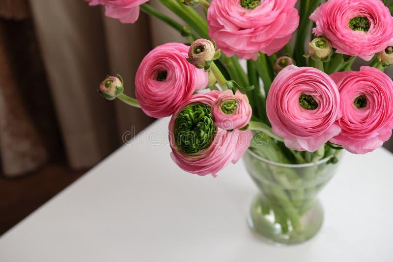 在透明玻璃花瓶的桃红色毛茛属花束在白色桌上 r 对花交付,社会媒介 r 免版税库存照片