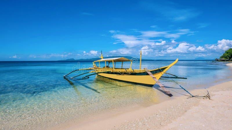 在透明的水中停住的一条黄色舷外架小船一白色沙滩在菲律宾 免版税库存照片