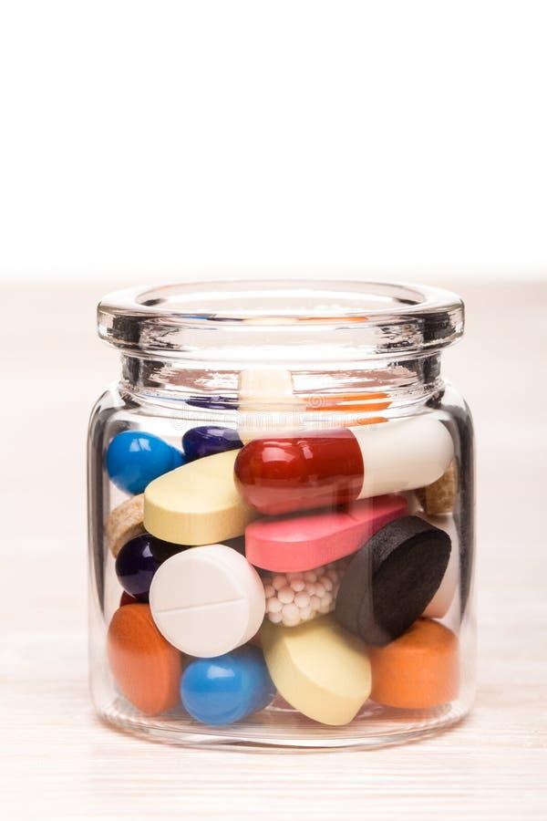在透明玻璃容器的色的药片 免版税库存照片
