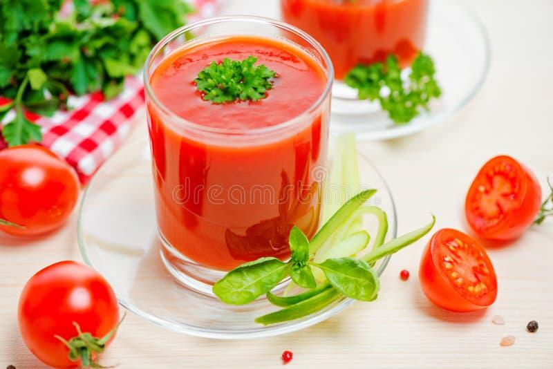 在透明玻璃的西红柿汁用荷兰芹和黄瓜 图库摄影