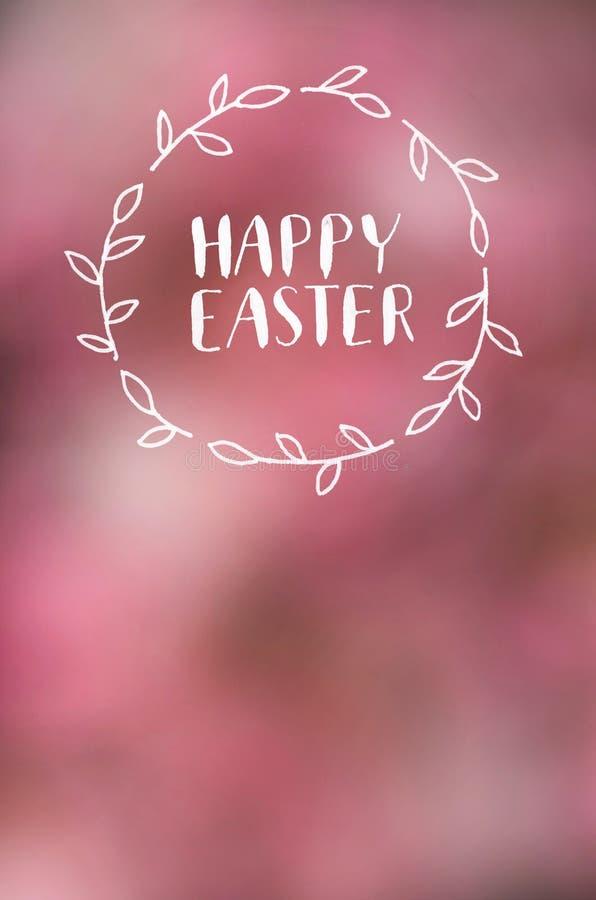 在透镜defocused桃红色开花背景的复活节快乐书法上写字 假日明信片,海报,横幅,贺卡 图库摄影