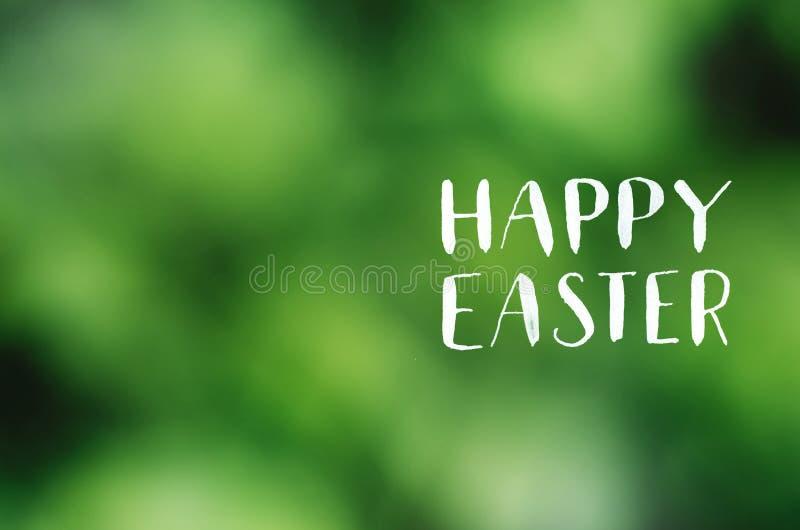 在透镜defocused绿色背景的复活节快乐书法上写字 假日明信片,海报,横幅,贺卡模板 库存图片