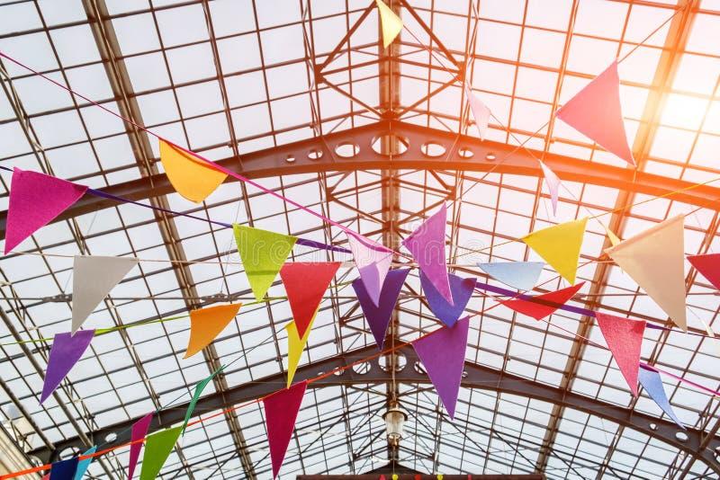 在透雕细工金属天花板下的许多五颜六色的旗子 图库摄影