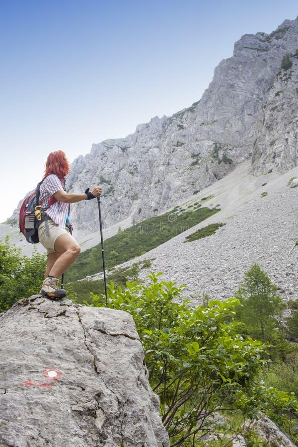 在途中的妇女远足者对山峰,在晴天,反对清楚的蓝天,文本的空间 库存图片