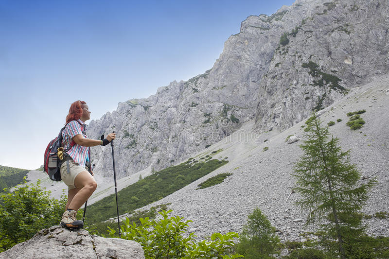在途中的妇女远足者对山峰,在晴天,反对清楚的蓝天,文本的空间 免版税库存照片