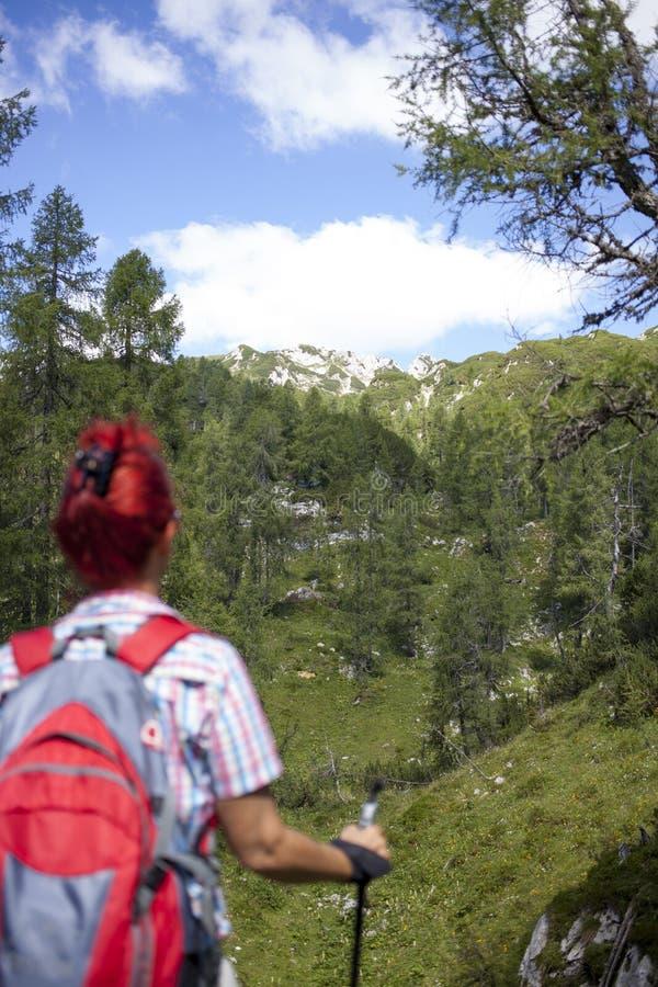 在途中的妇女远足者对山峰 库存图片