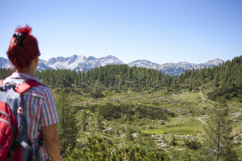 在途中的妇女远足者对山峰 图库摄影