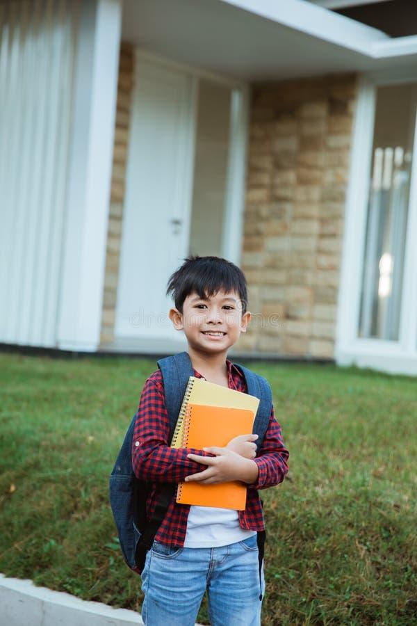 在途中的小学生对他的与背包和书的学校身分 免版税库存照片