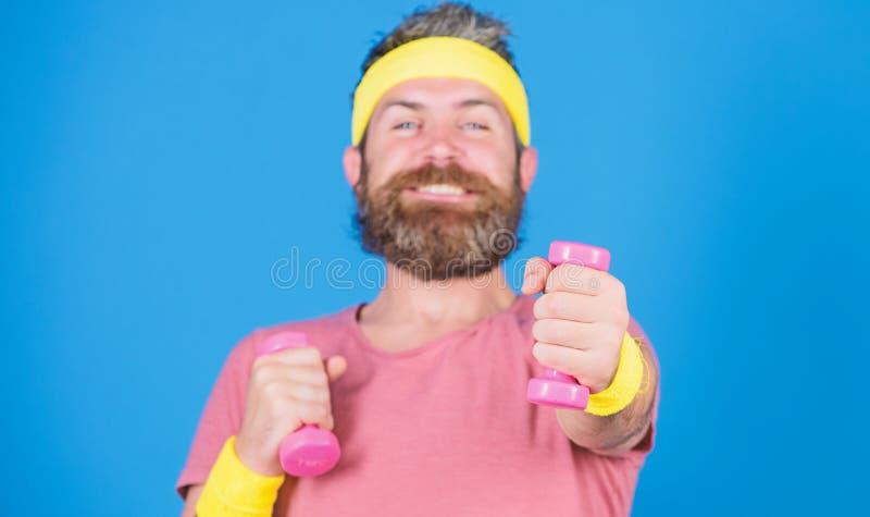 在途中的运动员对更强的身体 健康习性 与一点哑铃的运动员训练 人有胡子运动员行使 免版税库存图片