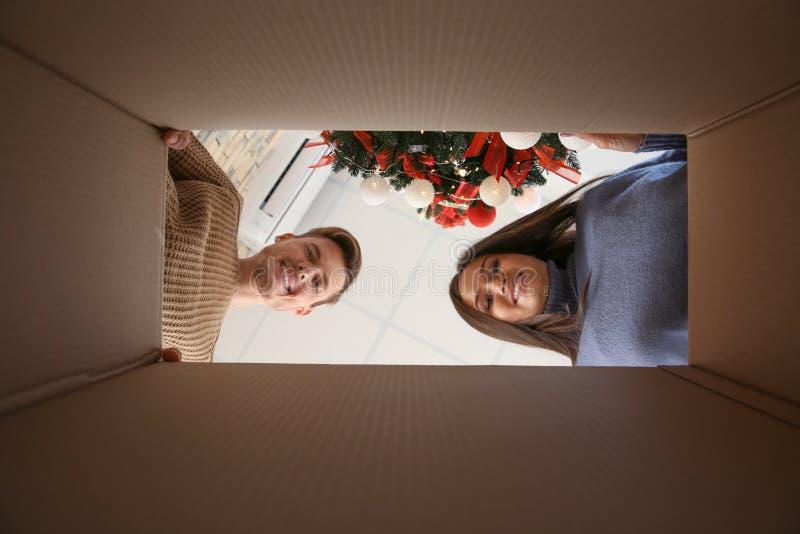 在逗人喜爱的年轻夫妇的看法从纸板箱的里面有圣诞节装饰的 免版税库存照片