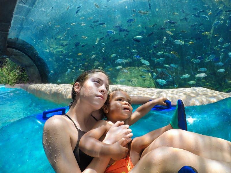 在通过水乘驾的两个孩子与一个大水族馆 免版税库存图片