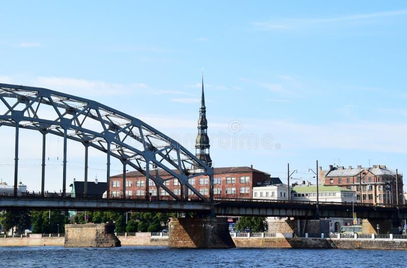 在道加瓦河河的铁路桥有圣彼得教会的看法,里加,拉脱维亚 库存照片