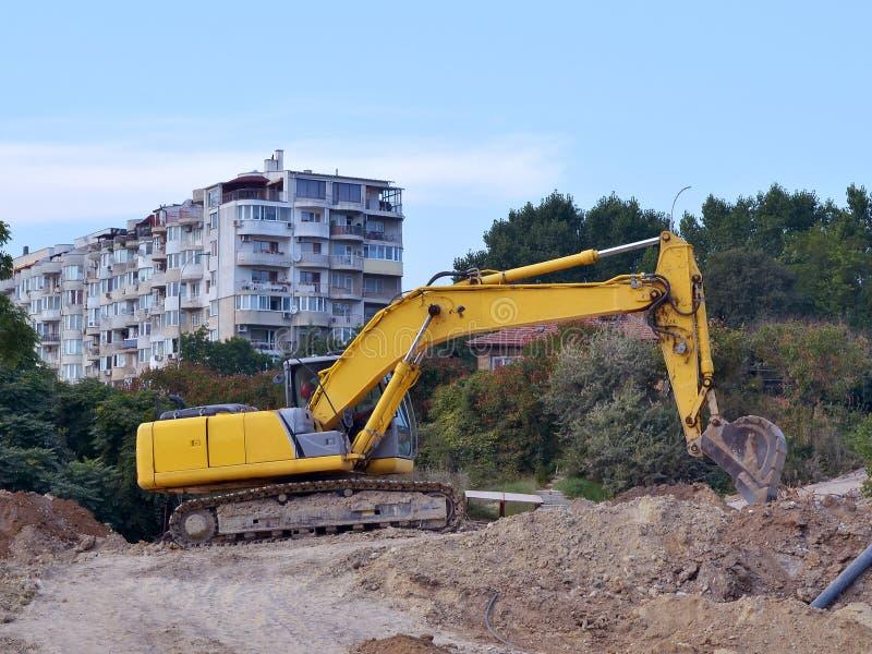 在道路施工工作的站点的黄色挖掘机在居民住房附近的 免版税库存图片