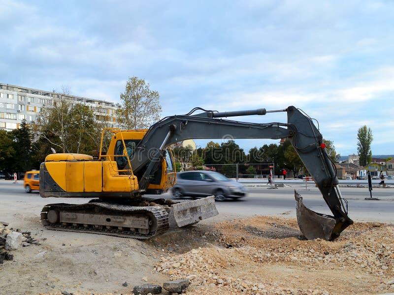 在道路施工工作站点的黄色履带牵引装置挖掘机在城市 图库摄影