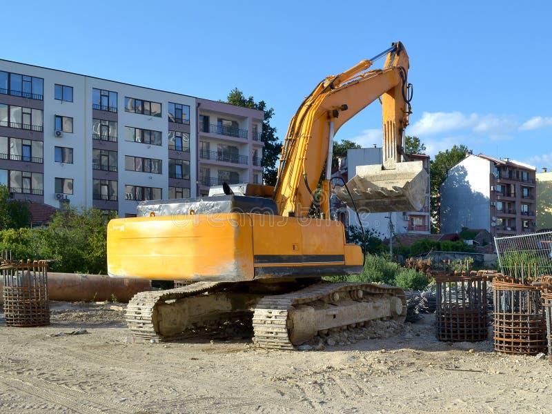 在道路施工工作站点的黄色挖掘机  库存图片