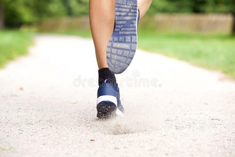 在道路的女性赛跑者鞋子 库存图片