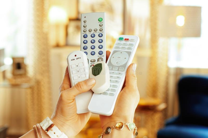 在遥控的特写镜头在现代妇女的手上 免版税库存照片