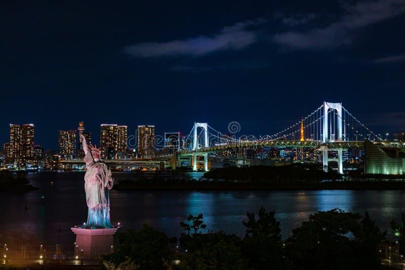 在遥远和东京铁塔看见的御台场的彩虹桥反对夜空和自由女神像在前景 免版税库存图片