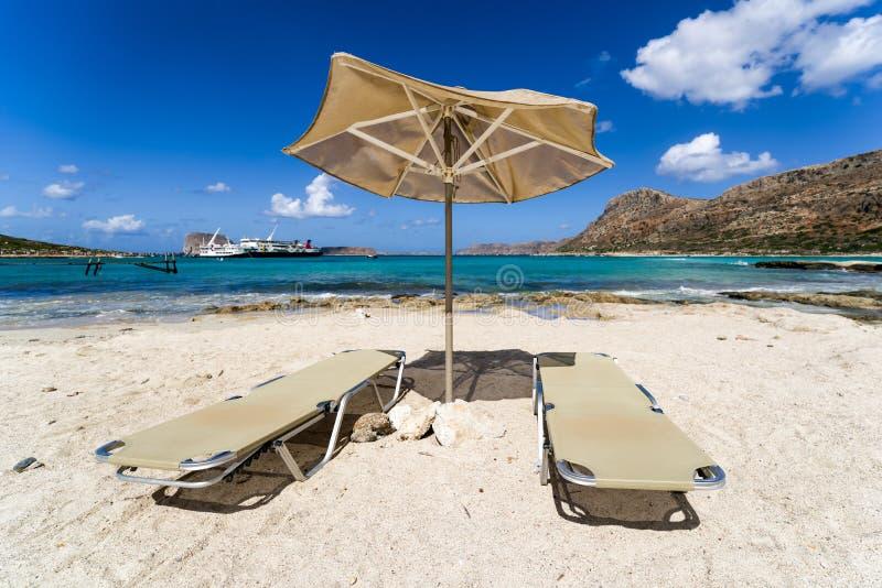 在遮光罩下的空的懒人在沙滩 免版税库存图片