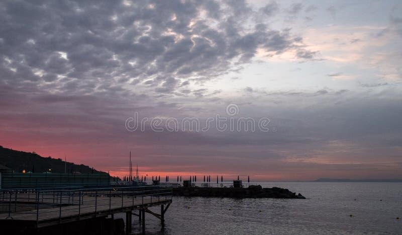 在那不勒斯海湾的看法在索伦托,日落的意大利附近的 在剪影的码头 免版税库存图片