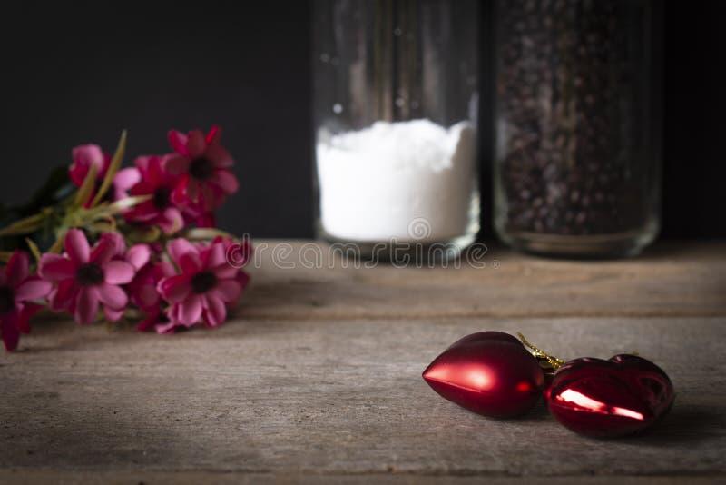 在那里一张木桌安置的红色塑料心脏是在左后面安置的花,并且有 库存图片