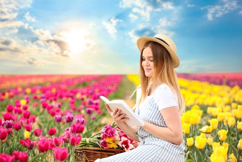 在郁金香领域的美丽的年轻女人看书在春日 图库摄影