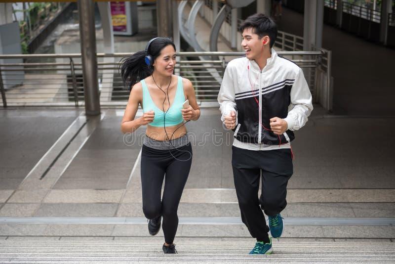 在都市城市跑的愉快的亚洲夫妇 库存照片